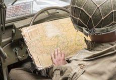 Conducteur d'un regard de véhicule militaire à une carte de la Normandie Photo stock