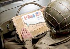 Conducteur d'un regard de véhicule militaire à une carte de la Normandie Images libres de droits