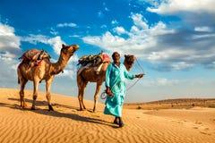 Conducteur de chameau de Cameleer avec des chameaux en dunes de Thar Photos stock