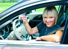 Conducteur de femme avec la clé de voiture Photographie stock libre de droits