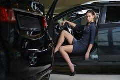 Conducteur de femme de beauté se reposant à l'intérieur de sa voiture avec la porte ouverte dans le parking Photographie stock