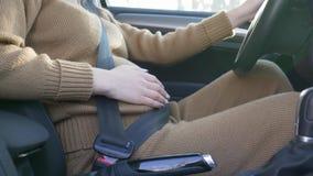 Conducteur de femme enceinte derrière la roue, ceinture de sécurité de port de soin de future mère frottant le ventre avec le fut banque de vidéos