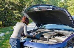Conducteur de femme regardant le moteur de elle voiture décomposée Photos stock