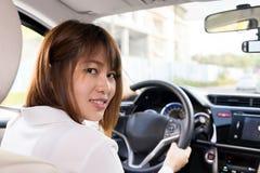 Conducteur de femme se reposant dans la voiture avec le sourire - soyez prêt pour conduire photographie stock