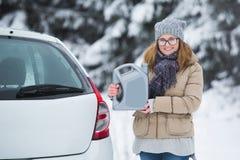 Conducteur de femme se tenant à côté de la voiture et des prises le jerrycan Photo stock