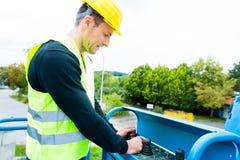 Conducteur de grue conduisant la rampe de levage hydraulique avec le pupitre de commande Image libre de droits