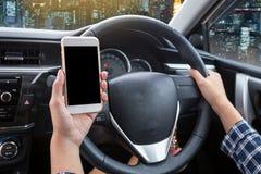 Conducteur de jeune femme à l'aide du smartphone et de la main d'écran tactile tenant le volant Photo stock