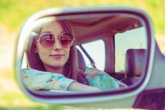 Conducteur de jeune femme dans la voiture regardant au miroir de vue de côté Photographie stock