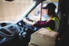 Conducteur de la livraison conduisant le fourgon avec des colis sur le siège photographie stock libre de droits