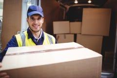 Conducteur de la livraison souriant à l'appareil-photo en son fourgon tenant le colis images libres de droits