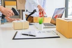 Conducteur de messager de service de distribution conduisant avec avec des boîtes dans des mains photo stock