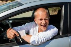 Conducteur enthousiaste tenant les clés de sa nouvelle voiture Images stock
