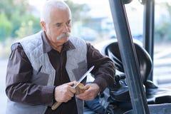 Conducteur expérimenté de chariot élévateur en dehors de chariot élévateur dans l'entrepôt Image libre de droits