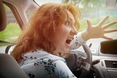 Conducteur fâché de femme criant tout en conduisant une voiture Photos stock