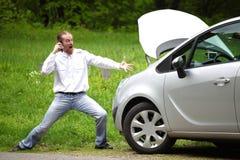 Conducteur furieux avec le téléphone portable une voiture cassée photographie stock