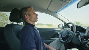 Conducteur masculin se reposant dans une voiture autonome, laissant la voiture conduire par lui-même banque de vidéos