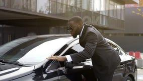 Conducteur personnel de personne importante essuyant la poussière de l'automobile chic et brillante image stock