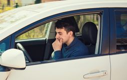 Conducteur réfléchi de jeune homme tenant sa main sous le menton semblant l'attente soucieuse dans sa voiture photo libre de droits