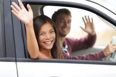 Conducteurs conduisant dans l'ondulation de voiture heureuse à l'appareil-photo Images stock