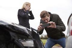 Conducteurs prenant la photo de l'accident de voiture aux téléphones portables Image stock