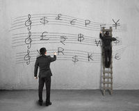 Conducting and another man drawing money stave on wall Stock Photography