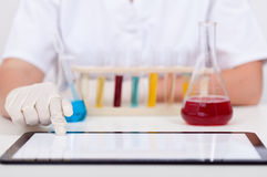 Conducting chemical experiments and documenting it on tablet com Royalty Free Stock Photos