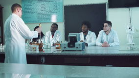 Conducting experiments at medical classes. Male lecturer in white coat conducting chemistry experiments in medical classroom with students sitting at desk stock footage