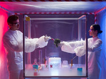 Conducting experiments on vegetables. Two scientists, a men and a woman, conducting chemical experiments on a piece of vegetable in a protection enclosure, in a Royalty Free Stock Images
