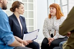 Conducting Group Therapy Session. Highly professional young psychologist listening to her obese patient suffering from eating disorder with concentration while stock images