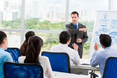 Conducting seminar. Middle-aged businessman conducting seminar for his colleagues Stock Photo
