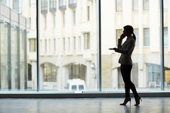 Conducting Telephone Negotiations. Profile view of unrecognizable businesswoman conducting telephone negotiations while standing at spacious office with Royalty Free Stock Photo