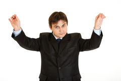 Conducting young businessman isolated on white Stock Image