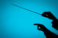 Conductor. Male orchestra conductor hands, one with baton. Silhouette against blue background Stock Photos