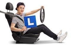Conductor adolescente en un asiento de carro que muestra una L-muestra Fotos de archivo libres de regalías