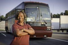 Conductor afroamericano del bus turístico que presenta delante del autobús Fotografía de archivo libre de regalías
