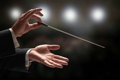 Conductor conducting an orchestra. With audience in background royalty free stock photography