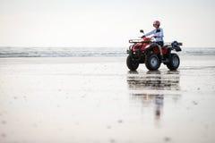 Conductor de ATV en la playa Imagenes de archivo