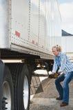 Conductor de camión de la mujer que levanta las piernas del acoplado imagenes de archivo