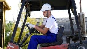 Conductor de camión de la carretilla elevadora en una fábrica o Warehouse que conduce entre las filas de la estantería con las pi