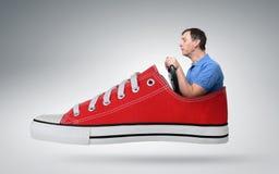 Conductor de coche divertido del hombre con una rueda en zapatilla de deporte roja Imagen de archivo libre de regalías