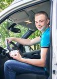 Conductor de coche Muchacho adolescente caucásico que muestra el carné de conducir en el nuevo Imagenes de archivo