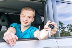Conductor de coche Muchacho adolescente caucásico que muestra llave del coche en el nuevo coche Imágenes de archivo libres de regalías