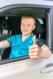 Conductor de coche Muchacho adolescente caucásico que muestra los pulgares para arriba, llave del coche y el ne Imagen de archivo libre de regalías