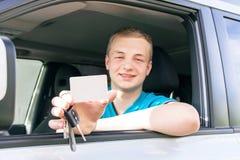 Conductor de coche Muchacho adolescente caucásico que muestra una tarjeta blanca vacía, coche Imagenes de archivo