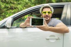 Conductor de coche que muestra la tableta digital con la pantalla en blanco imagenes de archivo