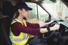 Conductor de la entrega que conduce la furgoneta con los paquetes en asiento fotografía de archivo