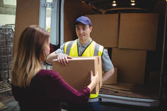 Conductor de la entrega que da el paquete al cliente fuera de la furgoneta Imágenes de archivo libres de regalías