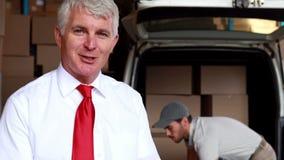 Conductor de la entrega que embala su furgoneta con el encargado que sonríe en la cámara almacen de metraje de vídeo