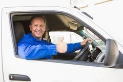 Conductor de la entrega que muestra los pulgares para arriba que conducen su furgoneta Imagen de archivo