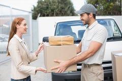 Conductor de la entrega que pasa paquetes al cliente feliz Foto de archivo libre de regalías